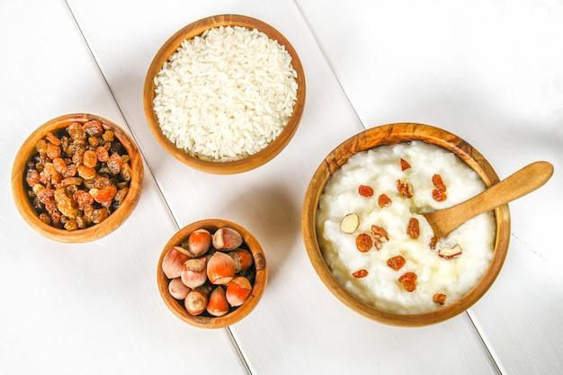 Rijstmelkpap met noten en rozijnen in houten kommen op een witte houten lijst Premium Foto