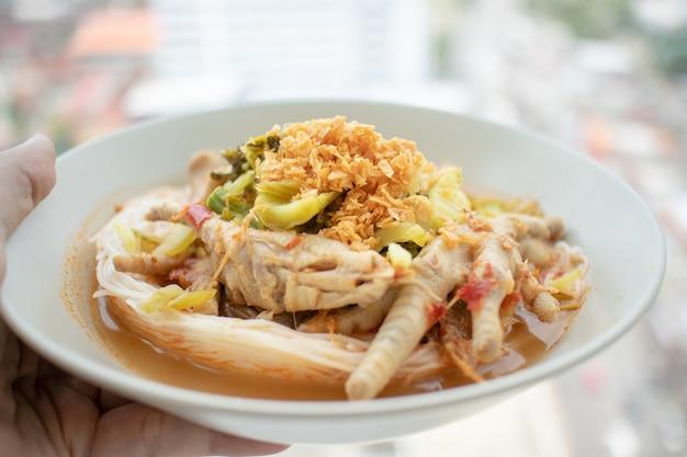 Rijstnoedels in viscurry-saus met kippenpoten. Premium Foto