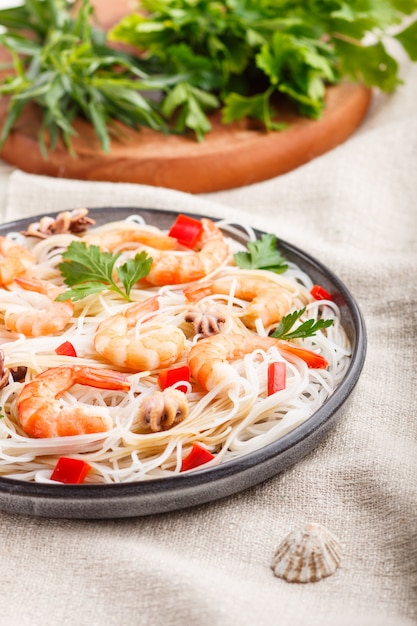 Rijstnoedels met garnalen of garnalen en kleine octopussen op grijze ceramische plaat op een witte linnen textiel selectieve nadruk Premium Foto