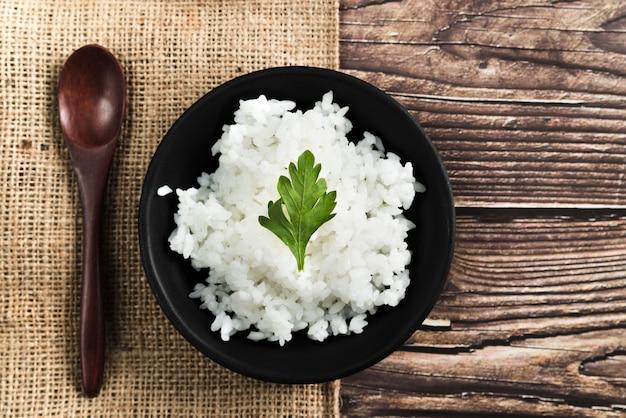 Rijstschotel met peterselie dichtbij houten lepel en jute Gratis Foto