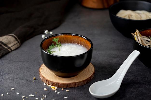 Rijstsoep in een zwarte kom op een houten steun en een witte lepel Gratis Foto