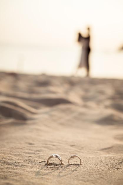 Ringen op strand met de silhouetten van de bruid en bruidegom Premium Foto