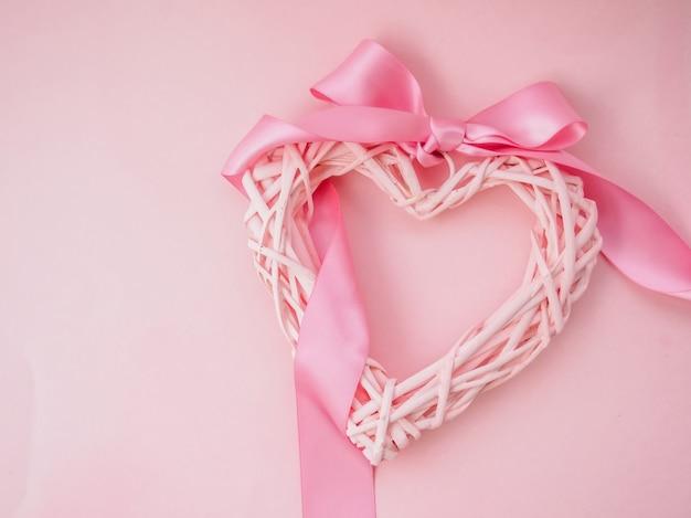 Rink gevlochten hart op roze basis met lint Premium Foto