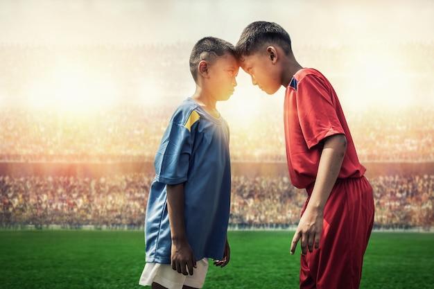 Rivaliserende voetbalkindjes in actie in het stadion Premium Foto