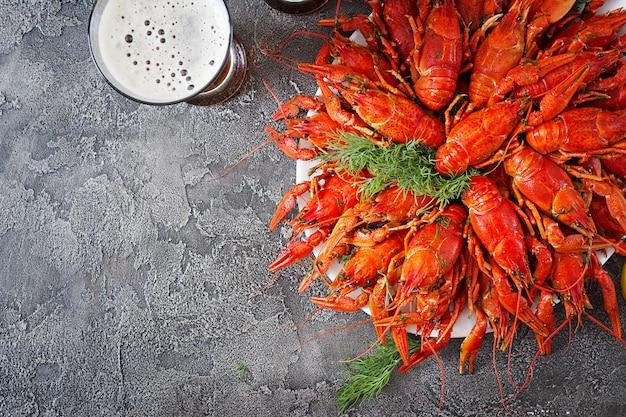 Rivierkreeft. rode gekookte langoesten op lijst in rustieke stijl, close-up. kreeft close-up. border desig. bovenaanzicht Gratis Foto