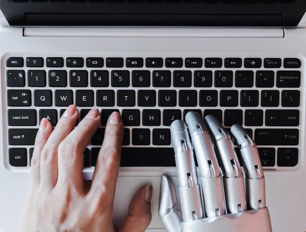 Robot handen en vingers wijzen naar laptop knop advisor chatbot robotachtige kunstmatige intelligentie concept Premium Foto