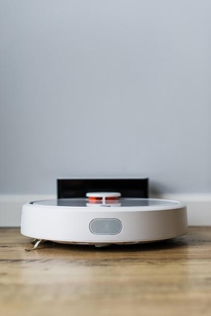 Robotstofzuiger op houten vloer. zijaanzicht. slim huisconcept. automatische reiniging. Premium Foto