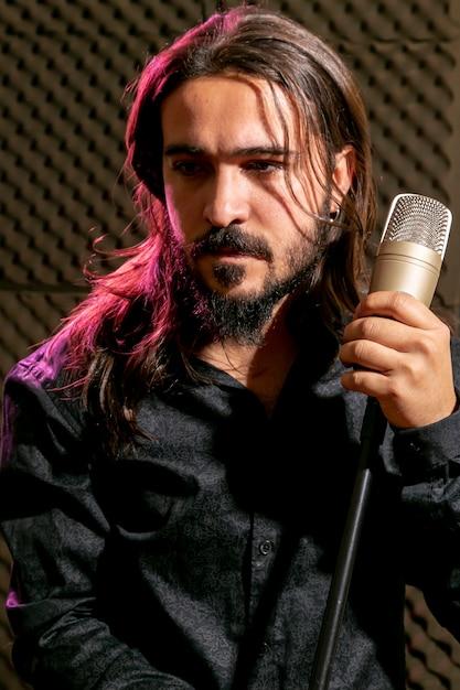 Rocker holding microfoon en wegkijken Gratis Foto