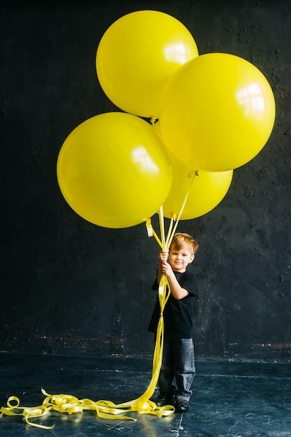 Rockster jongen met een grote gele ballonnen. stijlvolle baby in zwarte kleding op een zwarte achtergrond Premium Foto