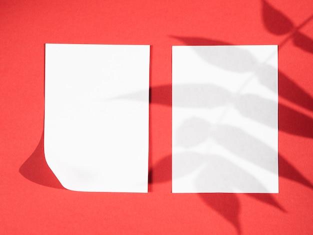 Rode achtergrond met witboeken en bladschaduwen Gratis Foto