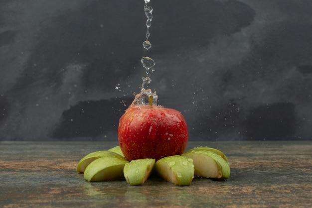 Rode appel met plakjes appel op marmeren oppervlak. Gratis Foto