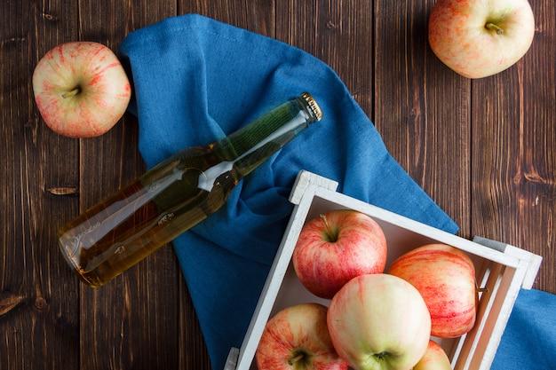 Rode appels in een houten doos en rond met appelsap bovenaanzicht op een blauwe doek en houten achtergrond Gratis Foto