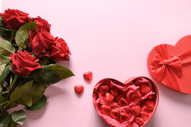 Rode chocoladesnoepjes en rozen op roze voor valentijnsdag. wenskaart met kopie ruimte. Premium Foto