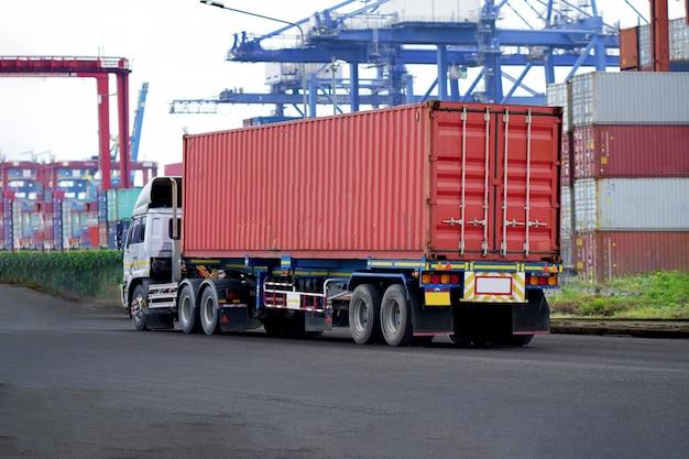 Rode containervrachtwagen in scheepshaven logistiek. transportindustrie in havenbedrijven. import, export logistieke industrie Premium Foto