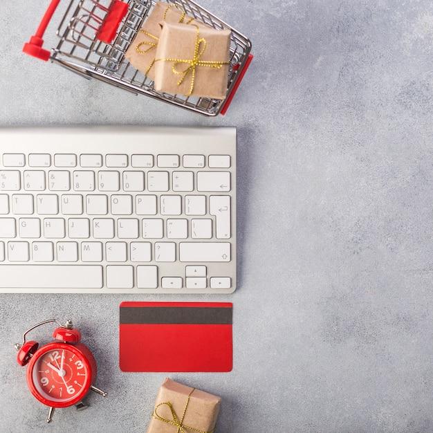 Rode creditcard, toetsenbord en kerstcadeautjes op grijze tafel plat lag, kopie ruimte. Premium Foto