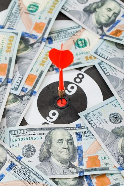 Rode dart in het midden van dartbord in bankbiljetten Gratis Foto