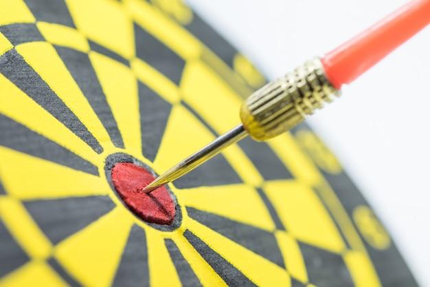 Rode dartpijl die in het doelcentrum van dartboard raakt. Premium Foto