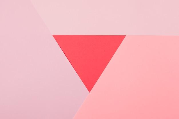 Rode driehoek die met roze document achtergrond wordt omringd Gratis Foto