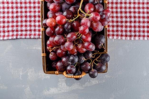 Rode druiven in een mand plat leggen op picknickdoek en gips Gratis Foto