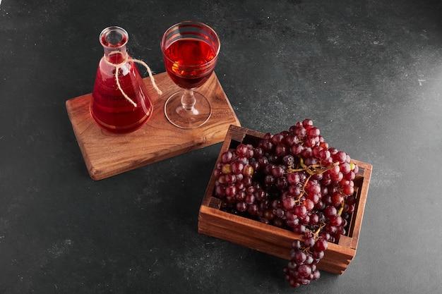 Rode druivenbossen in een houten dienblad met een glas wijn. Gratis Foto