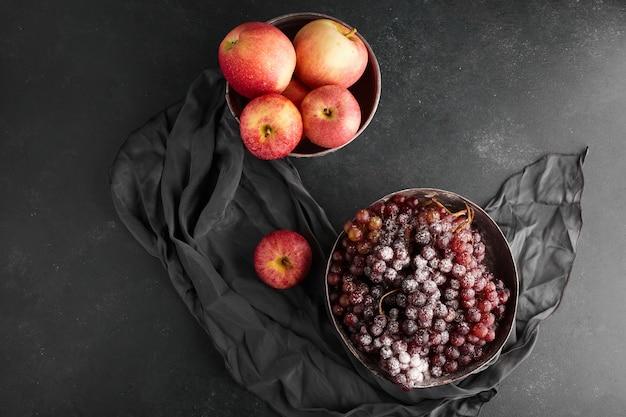 Rode druiventrossen en appels in metalen bekers, bovenaanzicht. Gratis Foto