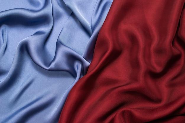 Rode en blauwe zijde of satijn luxe stof textuur. bovenaanzicht. Premium Foto