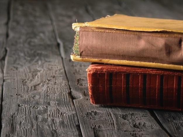 Rode en gele vintage boeken op een donkere houten tafel. literatuur uit het verleden. Premium Foto