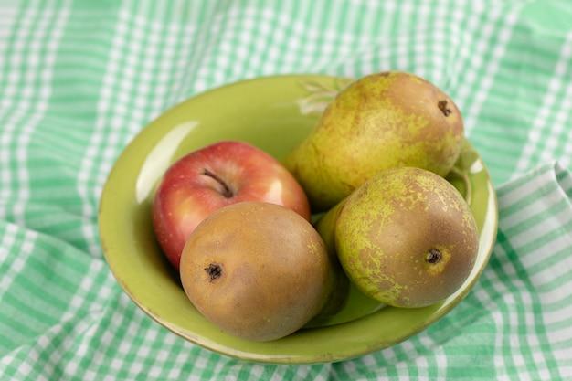 Rode en groene appels met verse peer in groene kom. Gratis Foto