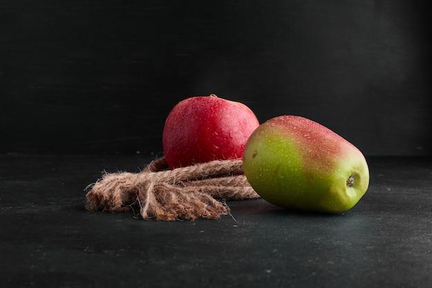 Rode en groene appels op zwarte achtergrond in het midden. Gratis Foto