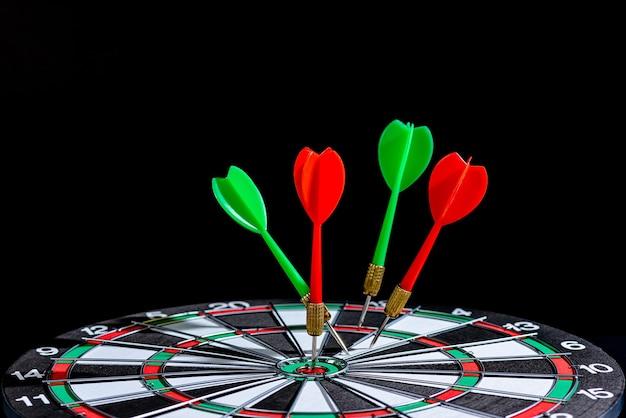 Rode en groene dartpijl die het doelcentrum raakt dartbord geïsoleerd, het stellen van het doeldoel bereiken concept uitdagende bedrijfsdoelen en klaar om het doel te bereiken Premium Foto
