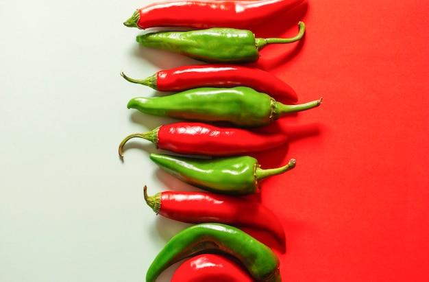 Rode en groene paprika's op een wit-rode ondergrond naast elkaar. Premium Foto