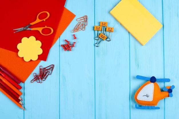 Rode en oranje briefpapier en voelde helikopter op blauwe houten achtergrond. Premium Foto