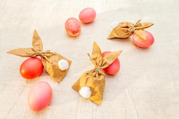 Rode en roze eieren voor pasen met papieren konijntjes Premium Foto