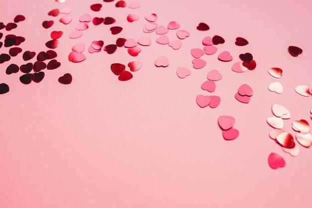 Rode en roze feestelijke achtergrond met rode hartvormige confetti. Premium Foto