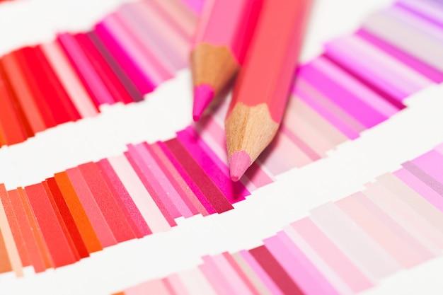 Rode en roze kleurpotloden en kleurenkaart van alle kleuren Premium Foto