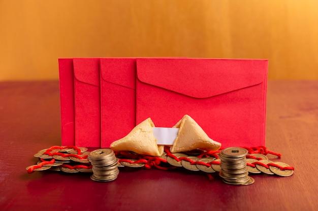Rode enveloppen met muntstukken en fortuinkoekjes voor chinees nieuw jaar Gratis Foto