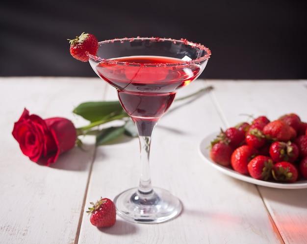 Rode exotische alcoholische cocktail in helder glas, bord met verse aardbeien en rode roos op de houten witte tafel voor een romantisch diner. Premium Foto