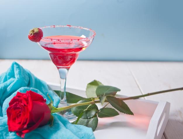 Rode exotische alcoholische cocktail in helder glas en rode roos op het houten witte dienblad voor een romantisch diner. Premium Foto