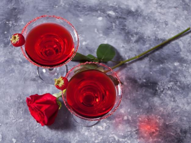 Rode exotische alcoholische cocktail in heldere glazen en rode roos voor een romantisch diner. Premium Foto