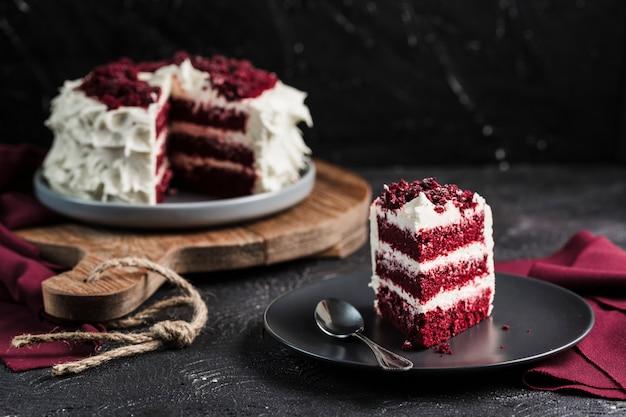 Rode fluweelcake op donkere achtergrond, close-up zijaanzicht. zoet dessert voor de vakantie. Premium Foto