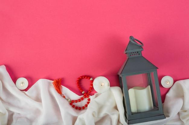 Rode gebedparels en kaarshouder met aangestoken kaars op witte doek over de rode achtergrond Gratis Foto