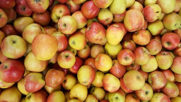 Rode gele appelenachtergrond in stapel van verse appelvruchten Premium Foto