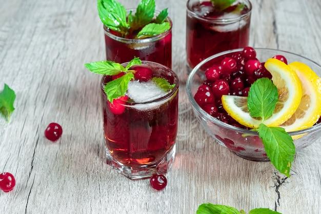 Rode glaswerk ontsproten alcoholische koude cocktail met de citroen en de munt van amerikaanse veenbessenframbozen Premium Foto