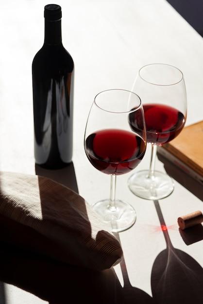 Rode glazen wijn naast een fles Gratis Foto