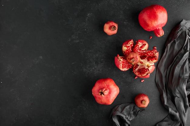 Rode granaatappels op zwart tafelkleed en oppervlak. Gratis Foto