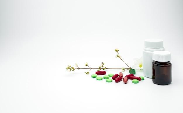 Rode, groene vitamine- en supplementtablet en capsulepillen met bloem en tak met blanco etiket plastic, oranje glazen fles op witte achtergrond met kopie ruimte, voeg gewoon uw eigen tekst toe Premium Foto