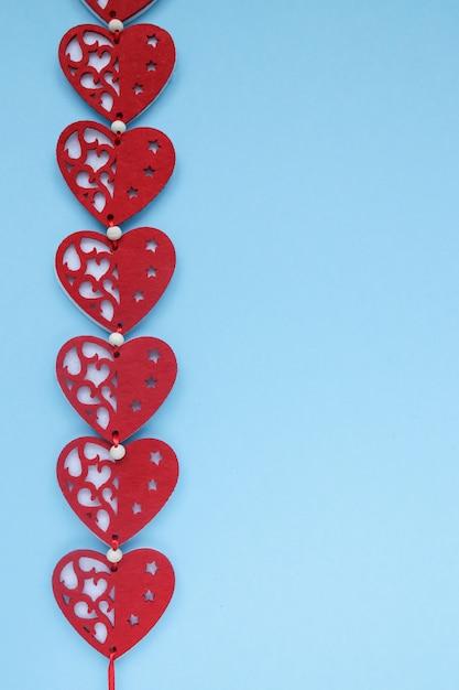 Rode harten op blauwe achtergrond. de achtergrond van de valentijnskaartendag met harten. copyplace, ruimte voor tekst en logo. Premium Foto
