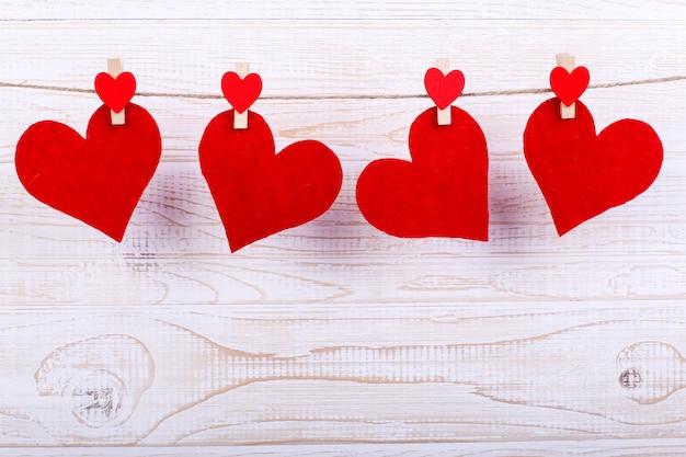 Rode harten op een touw met wasknijpers, op een witte houten achtergrond. plaats voor tekst, kopieer ruimte. Premium Foto