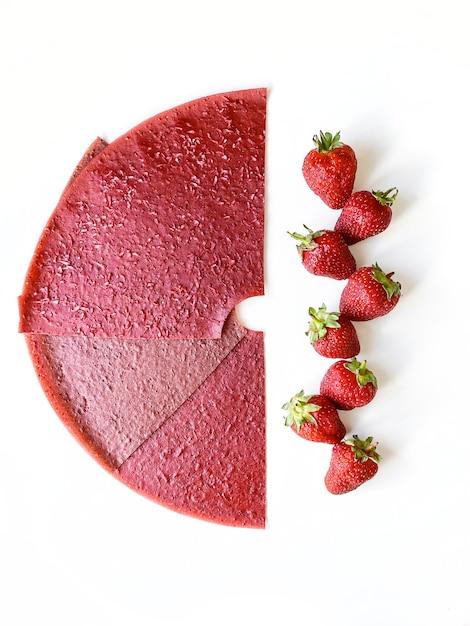 Rode het leerplakken en bessen van het aardbeifruit die op wit worden geïsoleerd. bovenaanzicht, plat gelegd. Premium Foto
