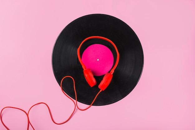 Rode hoofdtelefoon op vinylverslag over de roze achtergrond Gratis Foto